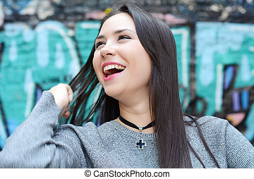 Portrait of young smiling woman outdoors.
