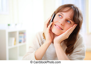Portrait of young smiling woman talking on telephone