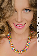 portrait of young smiling woman with necklaces