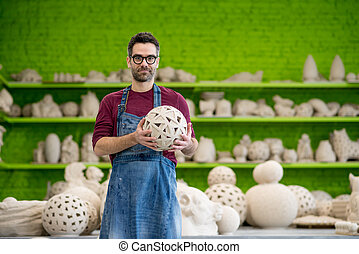 Portrait of Young SmilingCeramist in the Bright Modern Ceramic Workshop Holding Sculpture. Small Business Concept.