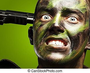 portrait of young soldier comiting suicide over green background