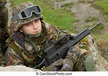 Portrait of young soldier sitting with a rifle