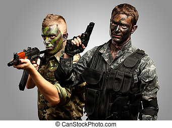 Portrait Of Young Soldier With Gun And Jungle Camouflage Paint