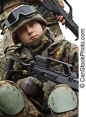 Portrait of young soldier with gun