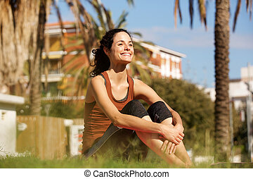 young sports woman resting on grass in park