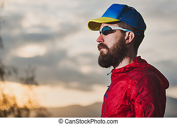Portrait of young sportsman with beard during resting in the mountains