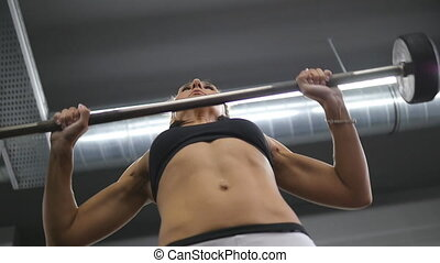 Portrait of young strong woman with fitness body in sportswear snatches heavy weight in gym. Female bodybuilder doing exercise - practicing deadlift. Girl training - lifting barbell. Slow motion