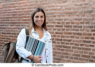 Portrait of young student girl on brick wall