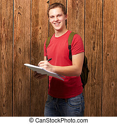 portrait of young student man writing on a notebook against a wooden wall