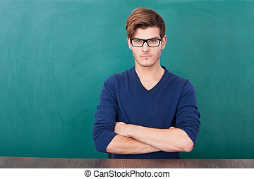 Young Student Standing In Front Of Chalkboard