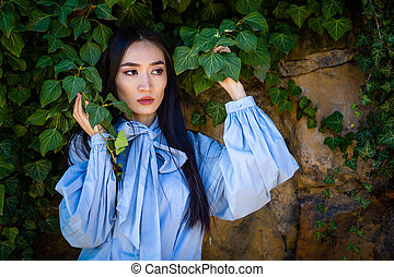 Portrait of young stylish asian woman in green leaves on wall background