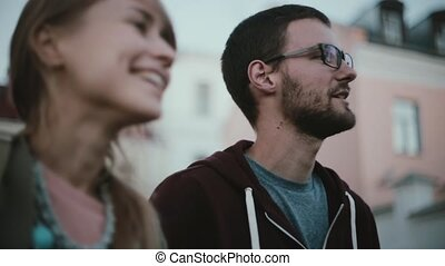 Portrait of young stylish couple standing in the city centre and talking. Friends spending time together in city centre.