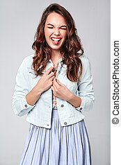 Portrait of young stylish laughing girl model in colorful casual summer clothes with natural makeup isolated on gray background. Looking at camera and showing her tongue