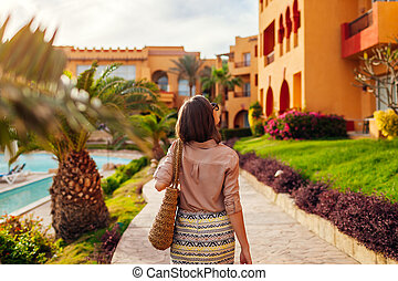 Portrait of young stylish woman walking on hotel territory in Egypt. Traveling concept