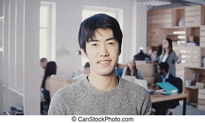 Portrait of young successful Asian businessman smiling at...