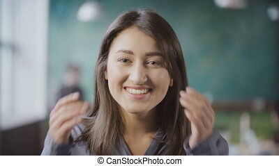 Portrait of young successful female employee. Asian woman entrepreneur worker in busy office, looks at camera, smile.