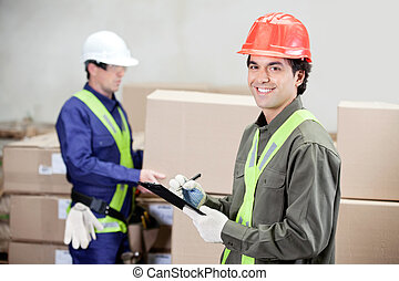 Portrait of young supervisor writing notes clipboard while foreman working at warehouse