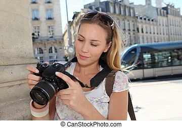 Portrait of young tourist looking at camera screen