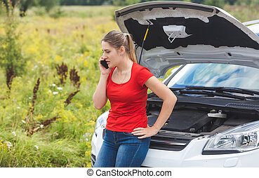 Portrait of young upset woman leaning on broken car in field and calling for help