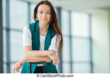 Portrait of young woman an airport lounge waiting for boarding