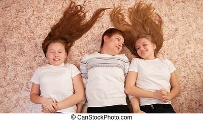 Portrait of young woman and two female teenagers lying on the floor at home, their feet on the couch