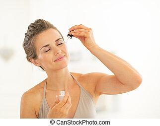 Portrait of young woman applying cosmetic elixir in bathroom