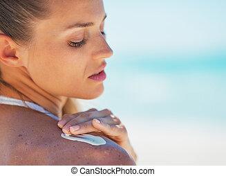 Portrait of young woman applying sun screen creme