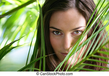 portrait of young woman behind foliage