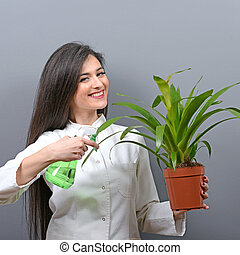 Portrait of young woman botanist watering plant against gray background