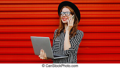 Portrait of young woman calling on smartphone with laptop over a red background