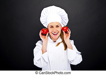Portrait of young woman chef with tomatos
