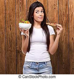 portrait of young woman choosing pizza or salad against a wooden wall