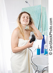 Portrait of young woman covered in towel drying hair in bathroom