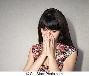 Portrait of young woman covering her face with hands.