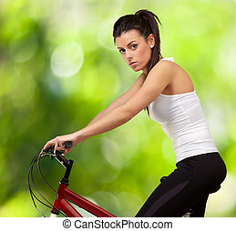 portrait of young woman cycling against a nature background