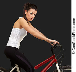 portrait of young woman cycling over black background