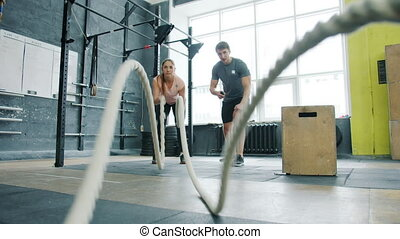 Portrait of young woman doing crossfit ropes battling ...