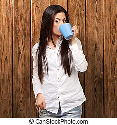 portrait of young woman drinking against a wooden wall