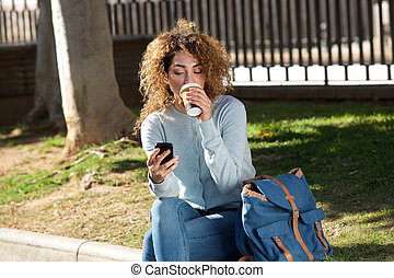 young woman drinking coffee and looking at cellphone