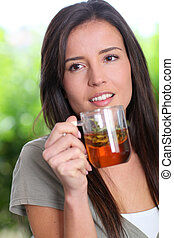 Portrait of young woman drinking herbal infusion