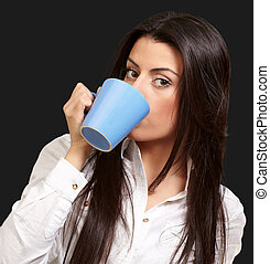portrait of young woman drinking over black background