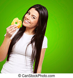 portrait of young woman eating a donut over green
