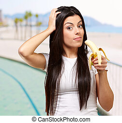 portrait of young woman eating banana near the beach