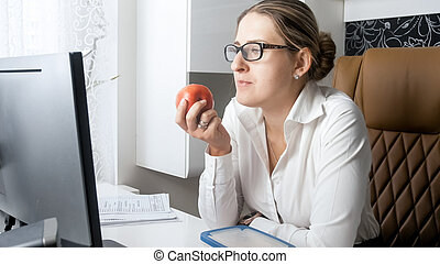 Portrait of young woman eating red apple during break at office