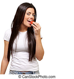 portrait of young woman eating strawberry against a white background