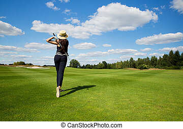 portrait of young woman golfer, back view