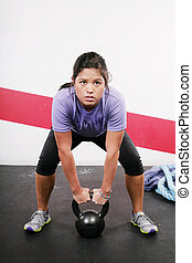 Portrait of young woman having a short break in her kettlebell crossfit workout