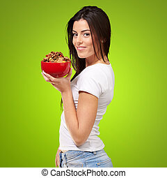portrait of young woman holding a cereal bowl over green background