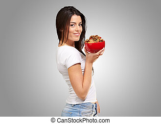 portrait of young woman holding a cereal bowl over grey background