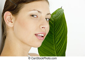 portrait of young woman holding a leaf